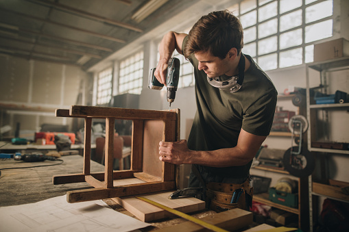 530997702 istock photo Male carpenter using drill to repair a chair in a workshop. 989178762