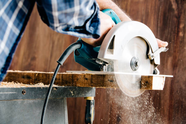 Male carpenter using electric circular saw in home workshop with wood chips flying stock photo