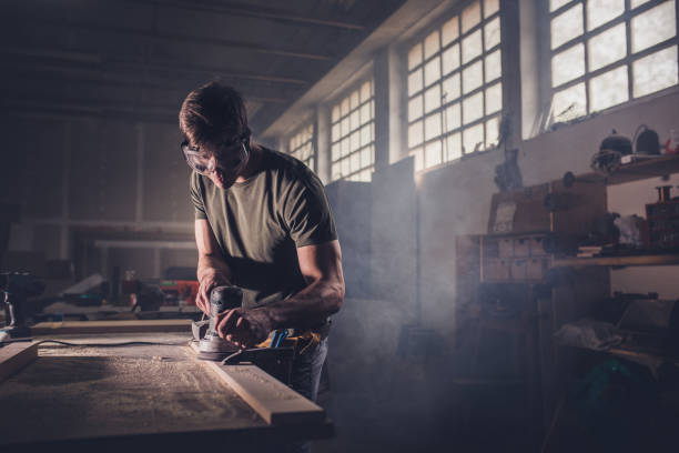 männliche zimmermann mit sander auf ein stück holz in einer tischlerei. - schmirgelmaschine stock-fotos und bilder