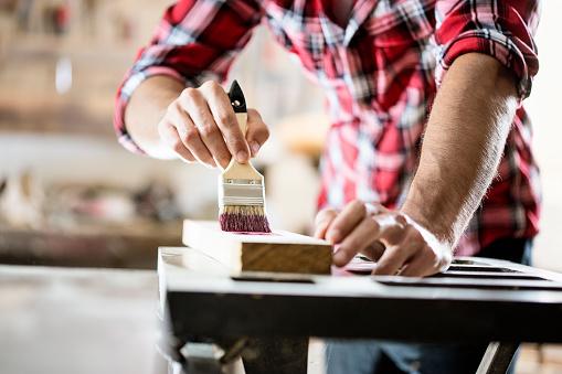 Male carpenter varnishing board close up