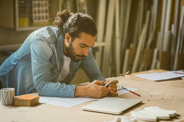 Male Carpenter Working In His Workshop Male carpenter working in his workshop. Examining blueprints and using smart phone, texting. He is focused on his work. man bun stock pictures, royalty-free photos & images