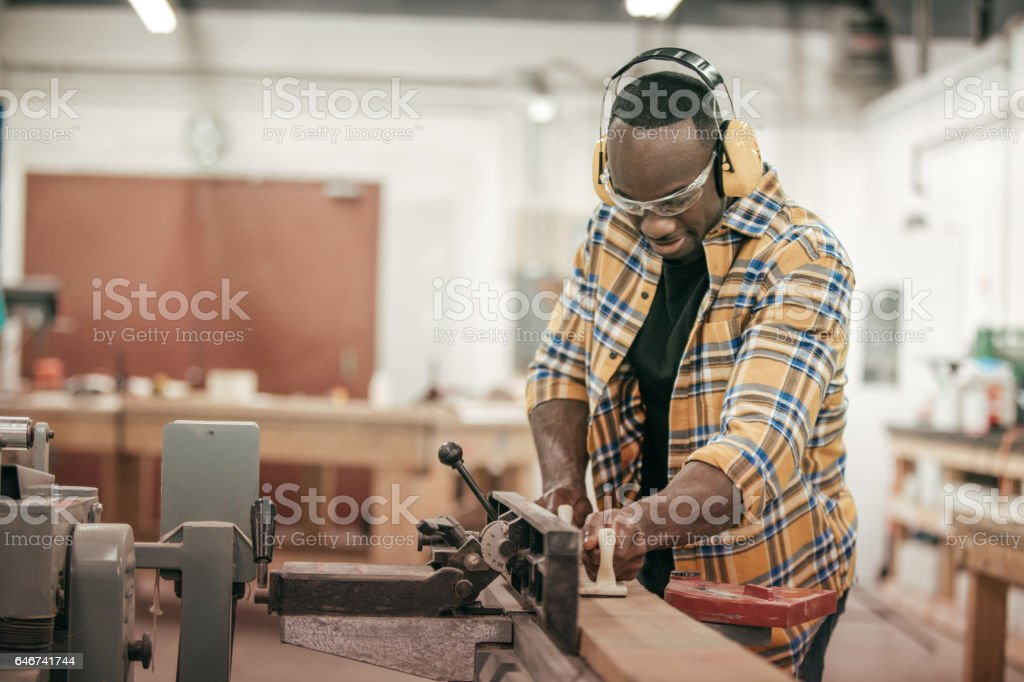 Male carpenter working with power tools in his wood shop stock photo