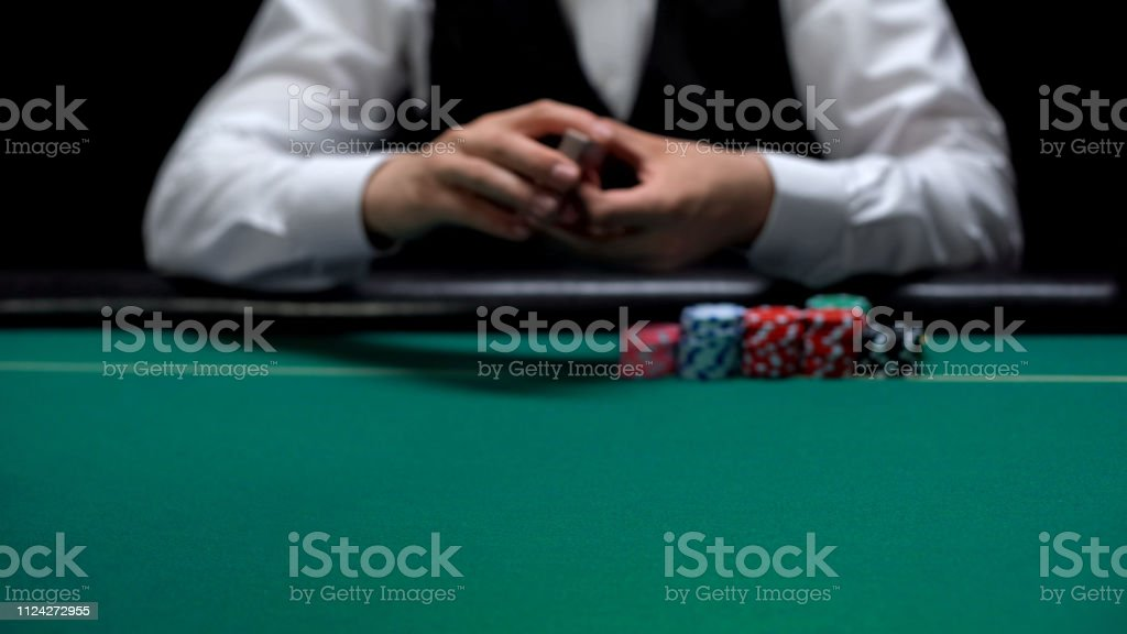 Male casino croupier holding playing cards, start of poker game,...
