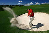 A male caucasian golfer wearing red shirt blasts out of bunker. Golf action shot. White man in his 30s demonstrating the proper technique, or short game skills, in hitting from a sand trap. Beautiful resort golf course in Canada. Model is a professional golfer.