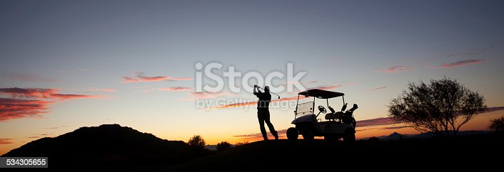 A male caucasian golfer swinging a golf club at dusk. Image taken in Arizona, United States, Panorama. The phoenix and Scottsdale region is one of the world's great golf destinations. There are well over a hundred beautiful desert golf courses in this region, which is known as the valley of the sun.