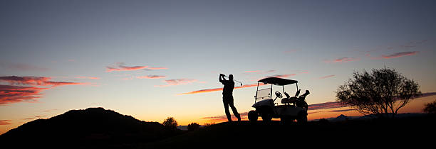 Male Caucasian Golfer Swinging A Golf Club with Cart stock photo