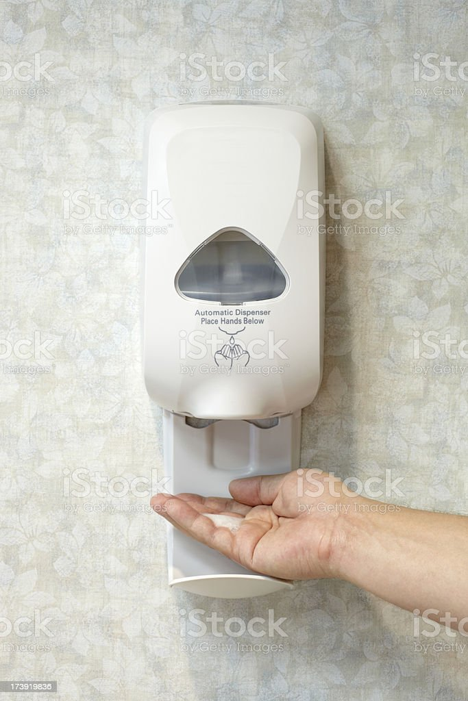 Male Caucasian Hand with Antibacterial Soap Sanitizer Dispenser stock photo