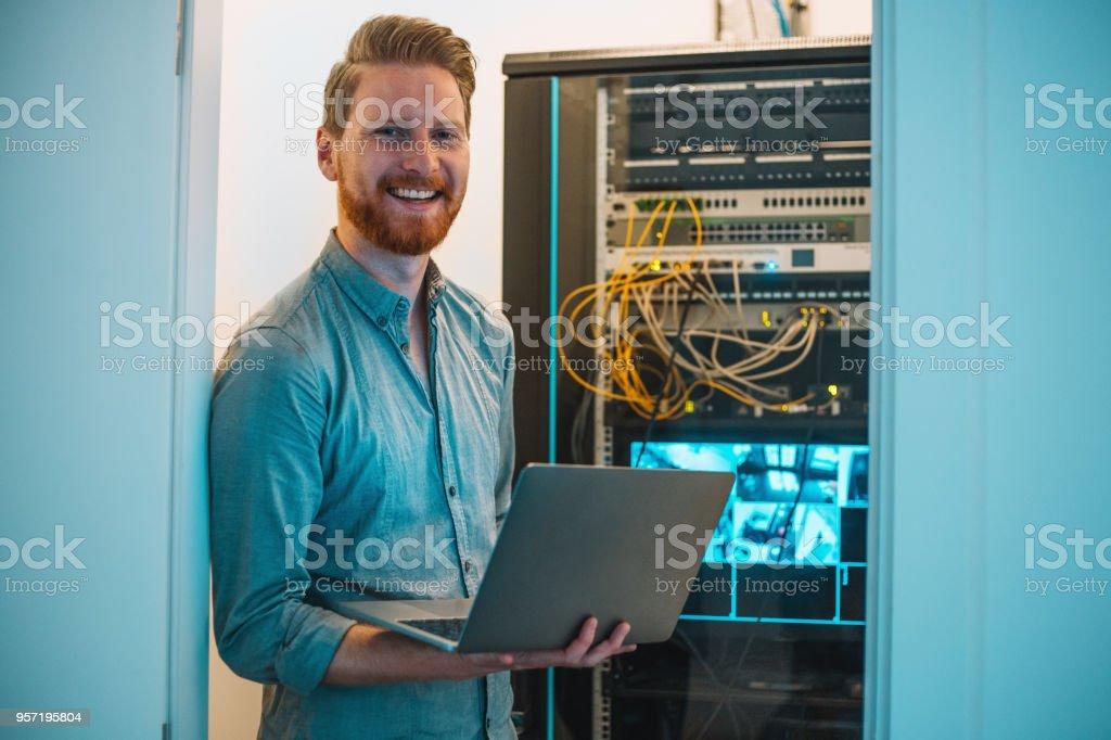 Male Caucasian IT technician using laptop in server room stock photo