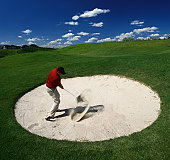 A golfer blasts out of a round sand bunker on a beautiful golf course in summer. Golfer is a male Caucasian in his 30s. He is demonstrating excellent form in blasting the ball out of the sand in an explosion shot. Good balance and swing technique for this type of shot. Wearing golf spikes, khaki pants, red golf shirt, black golf hat. Action shot at impact with sand flying. Beautiful blue summer sky. Square image.