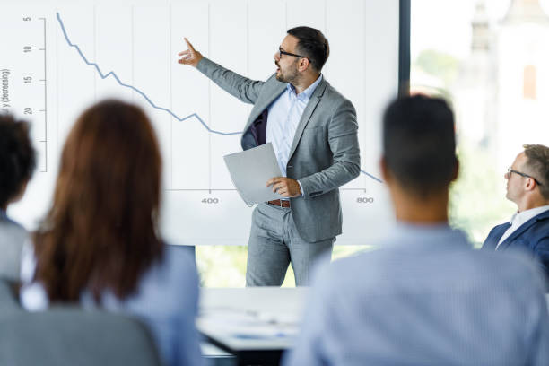Male CEO talking about economic crisis on presentation in the office. stock photo