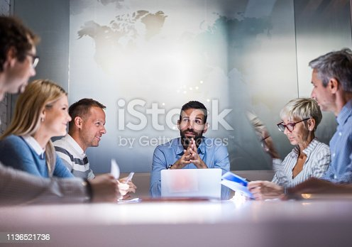 Smiling manager communicating with his team during a business meeting in a board room. Copy space.