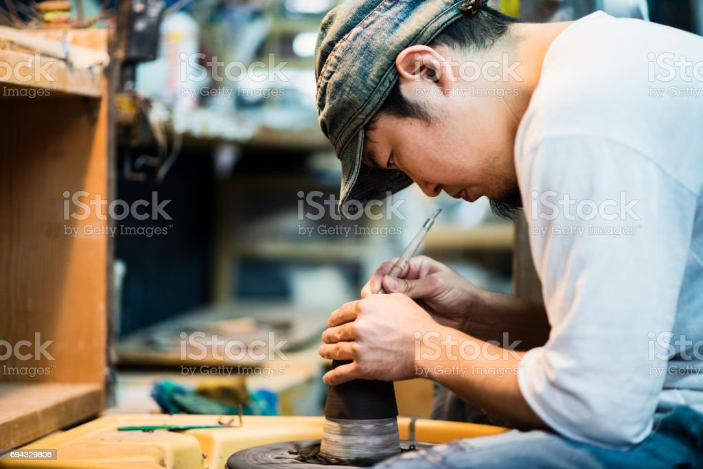 Mid adult man working in own ceramics Studio