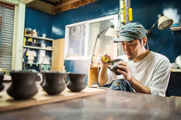 artistas de cerâmicas masculinas fazendo produtos em estúdio - cerâmica artesanato - fotografias e filmes do acervo