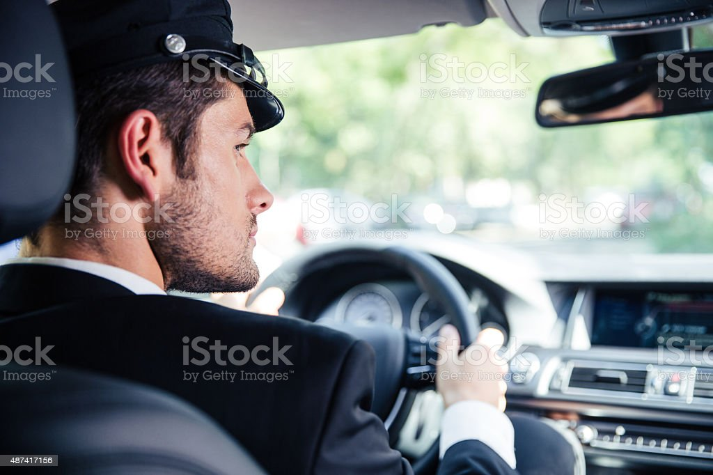 Male chauffeur riding car stock photo