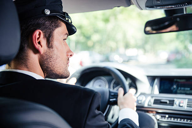 male chauffeur riding car - limousine service stock photos and pictures