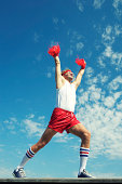 Male cheerleader in funky 70s outfit with long socks holds red pom poms in the air