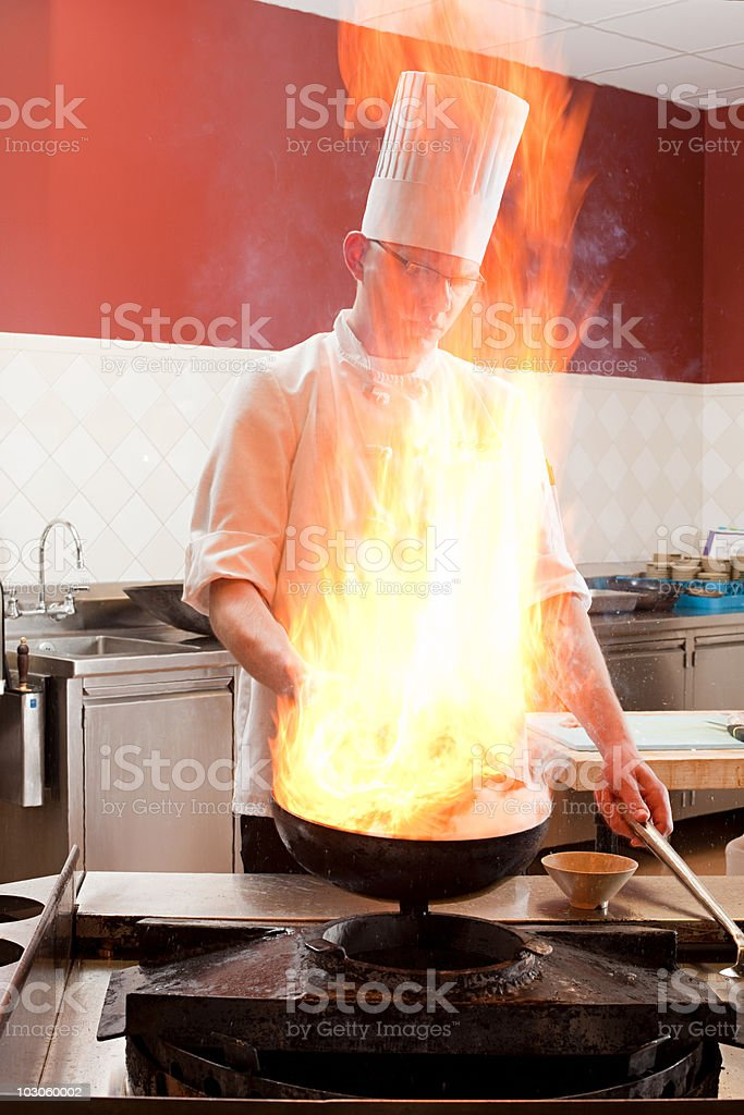 Male chef cooking food in commercial kitchen, flame over stove royalty-free stock photo