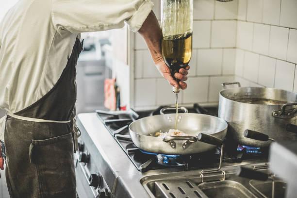 mannelijke chef-kok koken verse vis saus in de keuken van het restaurant - cook aan het werk tijdens diner service - italiaanse gerechten, levensstijl en gezonde voeding de concept - zich richten op zijn hand - oil kitchen stockfoto's en -beelden