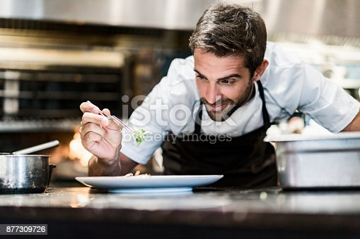 istock Male chef garnishing food in kitchen 877309726