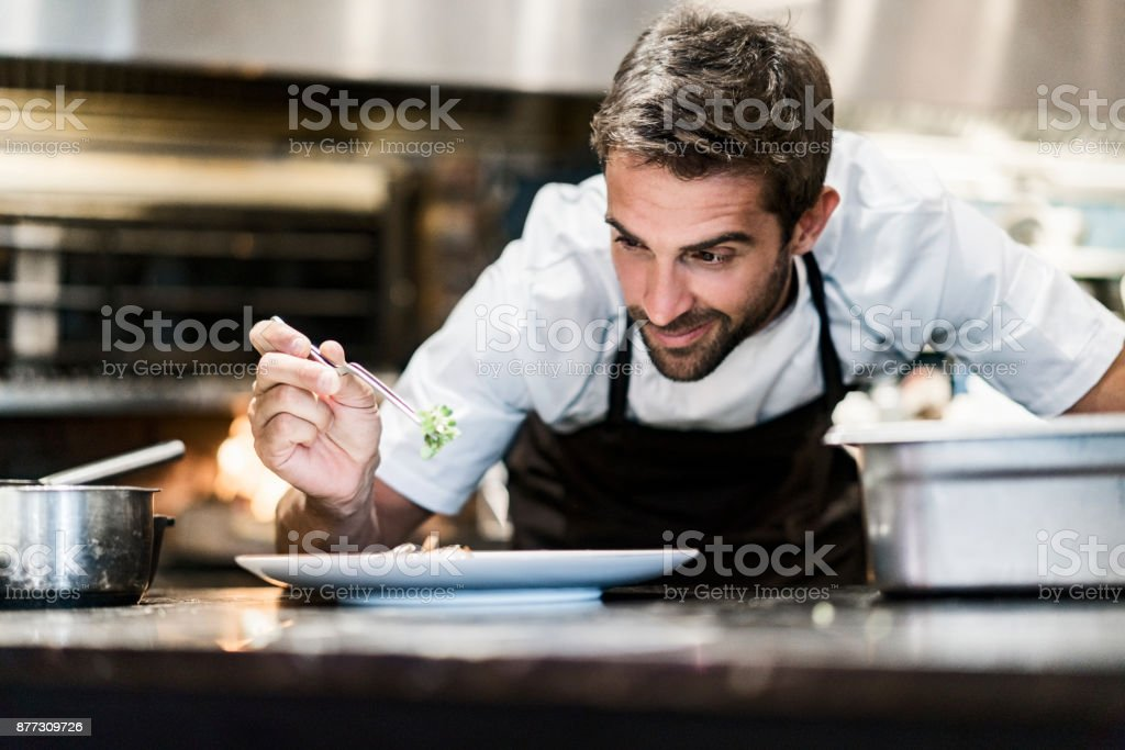Chef hombres guarnición de alimentos en cocina - foto de stock