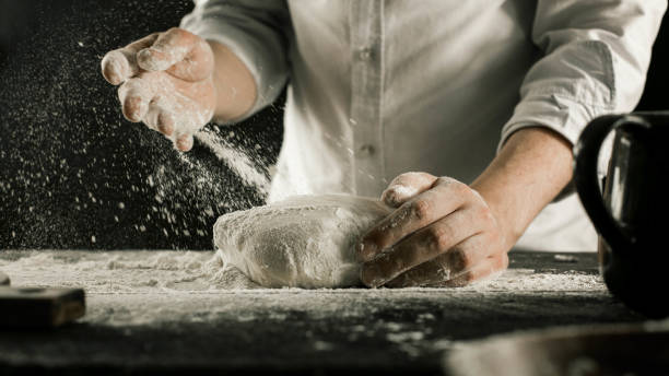 Male chef hands knead dough with flour on kitchen table Male chef hands knead dough with flour on kitchen table side view kneading dough stock pictures, royalty-free photos & images