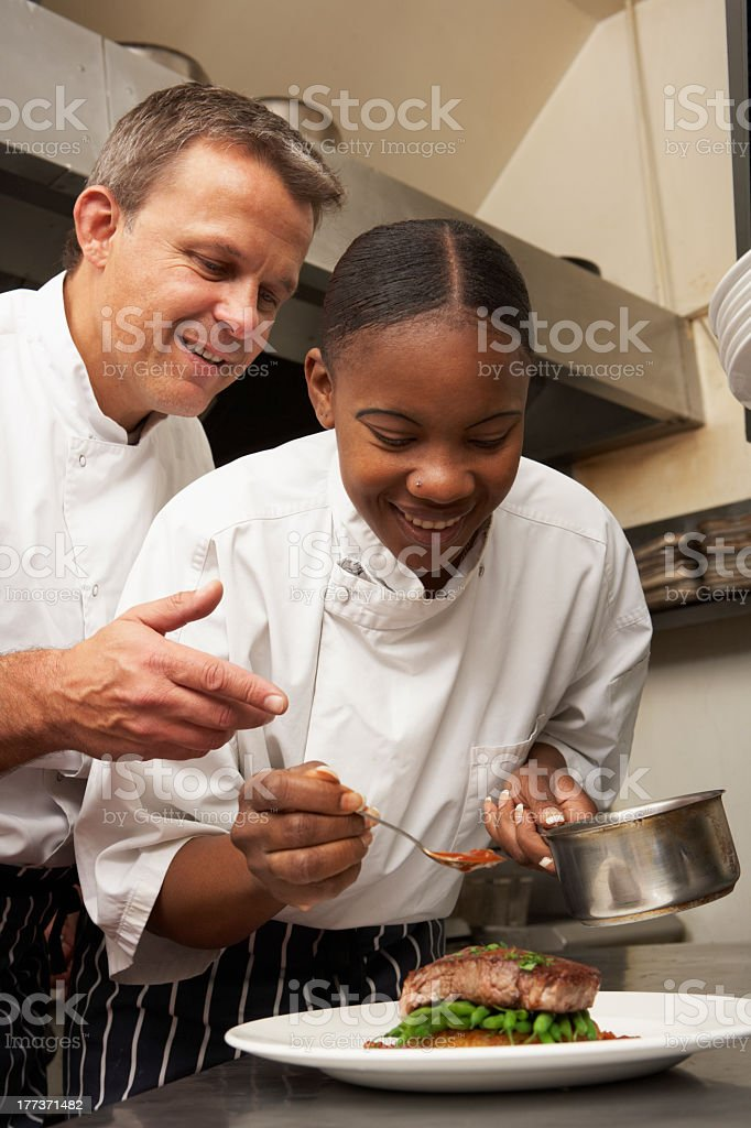 Male chef instructing female trainee in restaurant kitchen stock photo