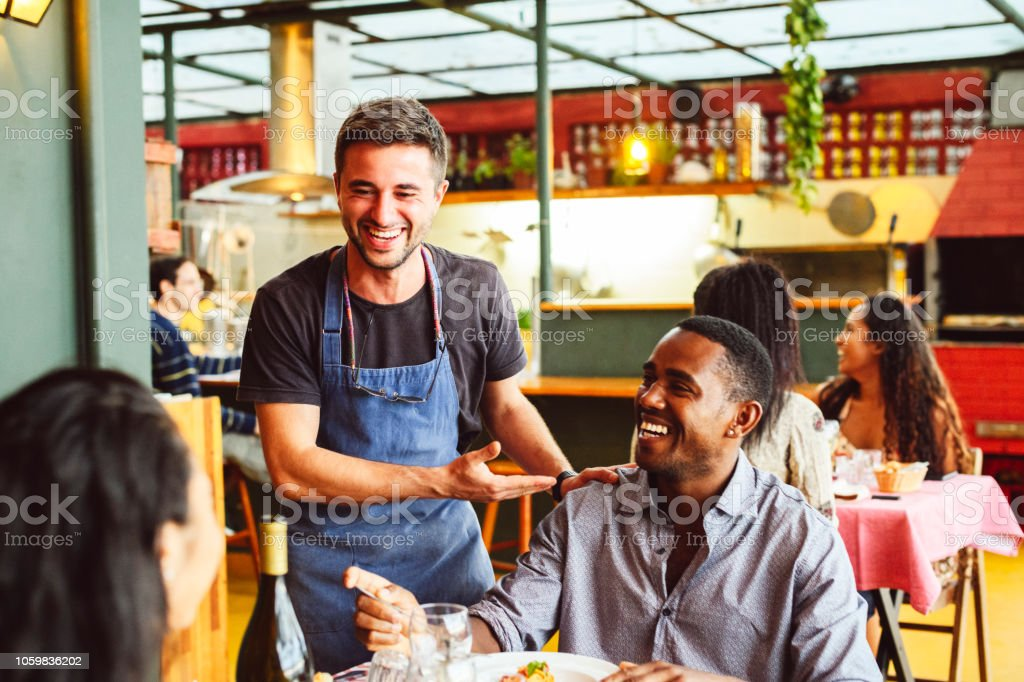 Male chef laughing and chatting with hand on shoulder of male customer Couple sitting opposite each other in small restaurant, waiter standing and socialising, relaxed and friendly, customer service 20-24 Years Stock Photo
