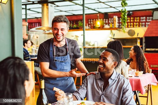 Couple sitting opposite each other in small restaurant, waiter standing and socialising, relaxed and friendly, customer service