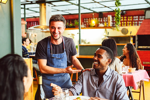 Male Chef Laughing And Chatting With Hand On Shoulder Of Male Customer Stock Photo - Download Image Now
