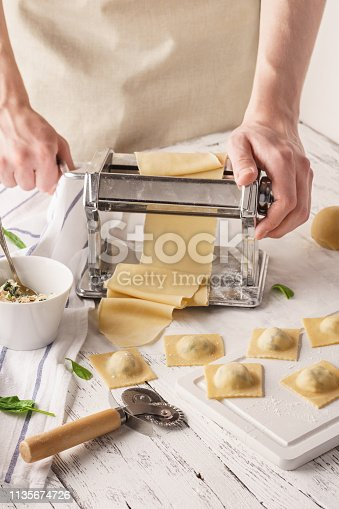 Male chef making ravioli with pasta machine. Cooking process.