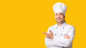 istock Male Chef Pointing Fingers Aside Standing On Yellow Background, Panorama 1208522535