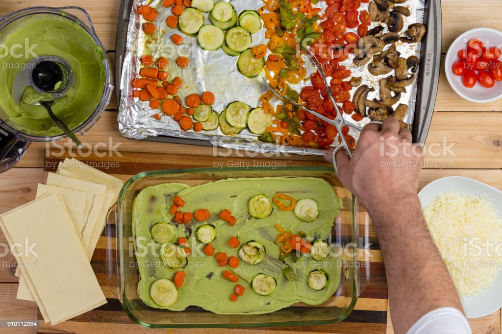 Male chef preparing a vegetable lasagne stock photo
