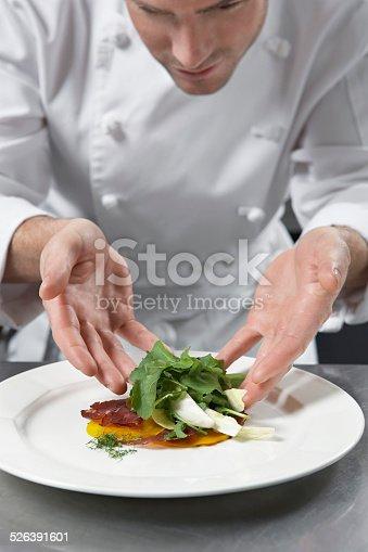 istock Male Chef Preparing Salad In Kitchen 526391601