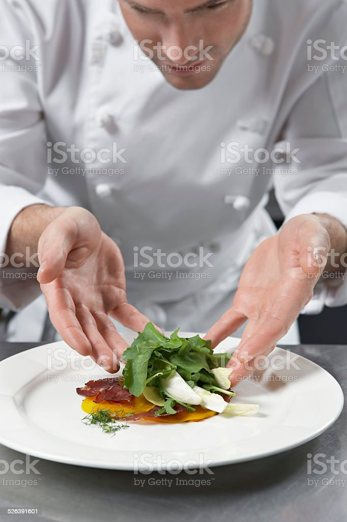 Male Chef Preparing Salad In Kitchen stock photo