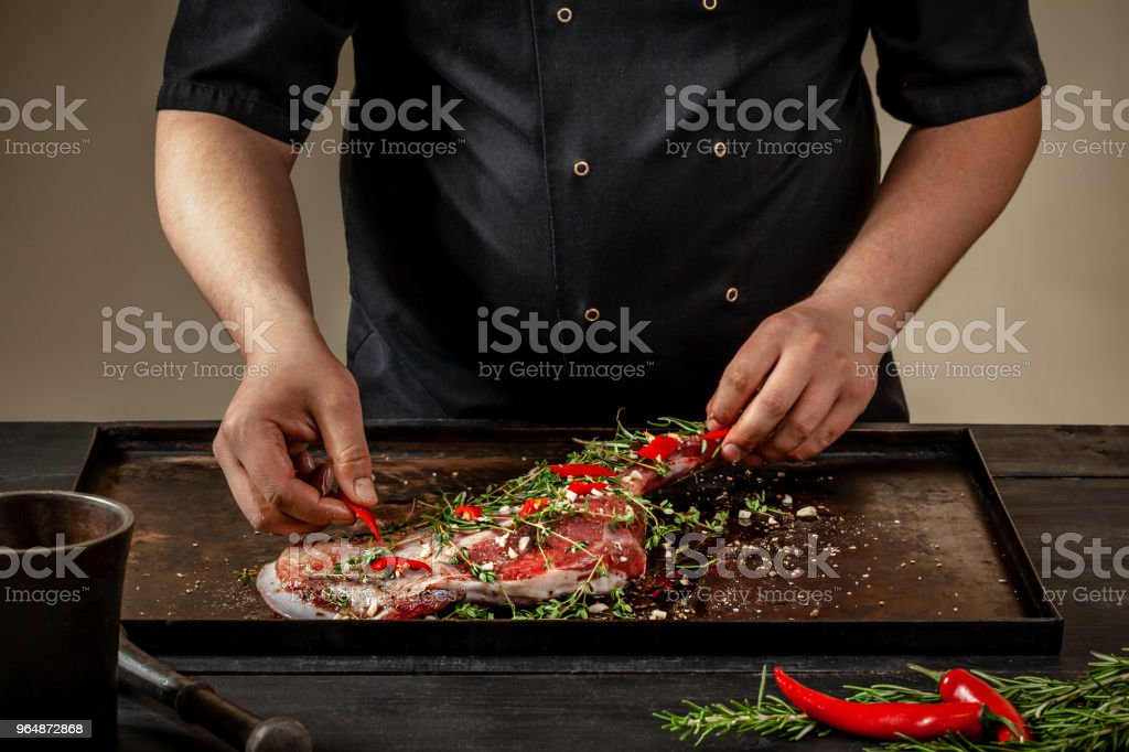 Male chef rubbing raw lamb shanks with greens and spices on stone tray on wooden table. Chef cooking appetizing shank of lamb royalty-free stock photo