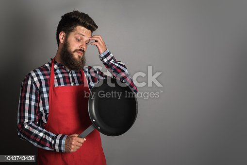 istock Male chef with frying pan 1043743436