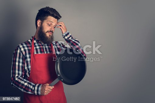 istock Male chef with frying pan 973547482