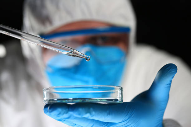 Male chemist look at microscope hold test tube stock photo