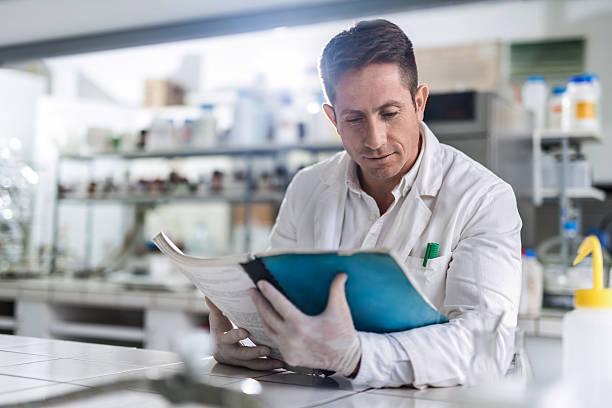 männliche chemiker lesung medizinischer daten im labor. - publikation stock-fotos und bilder
