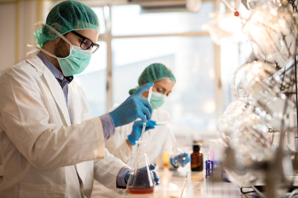Male chemist working with medical samples while working on scientific experiment. stock photo