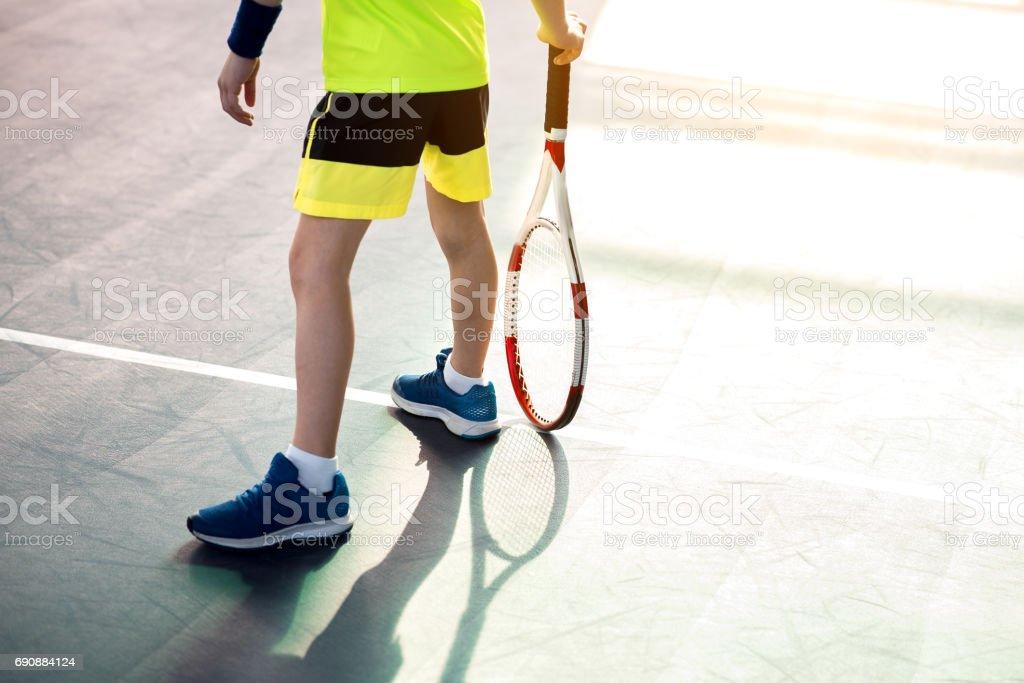 Male child playing tennis on playground stock photo