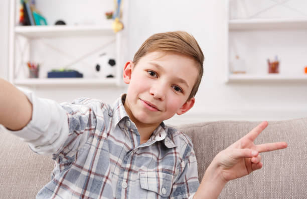 Male child taking selfie on phone at home stock photo