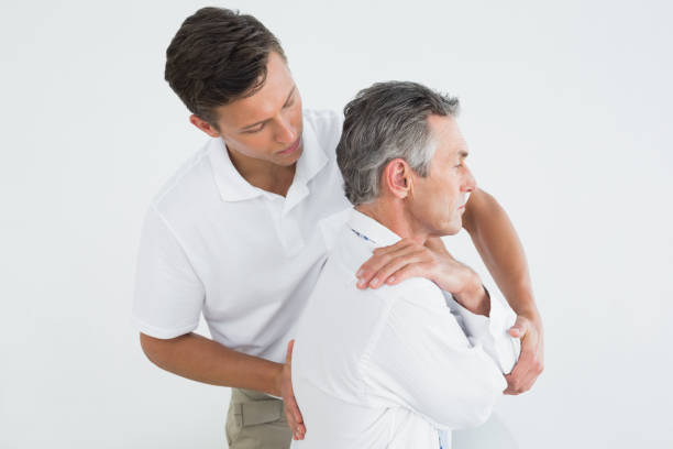 male chiropractor examining mature man - chiropractic care stock photos and pictures
