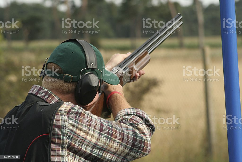 A male clay shooter holding a gun at his shoulder stock photo