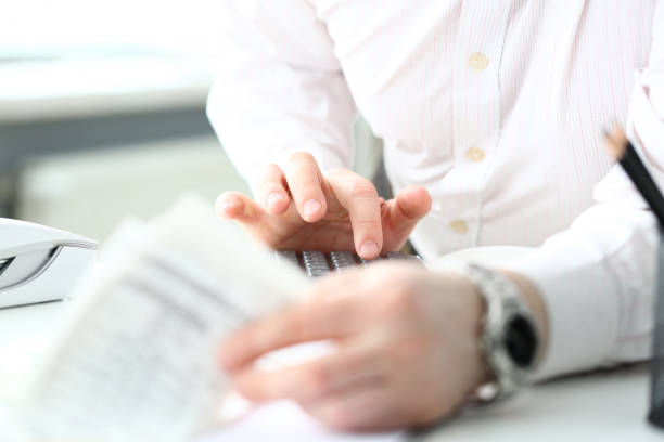 Male clerk finger pressing buttons on calculator devise evaluating expenses stock photo