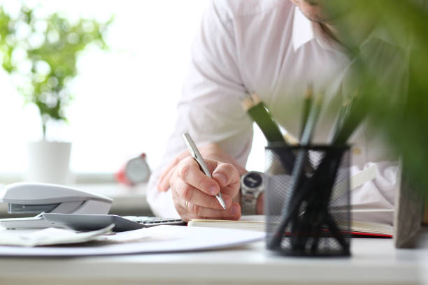Male clerk hand holding silver pen writing something stock photo
