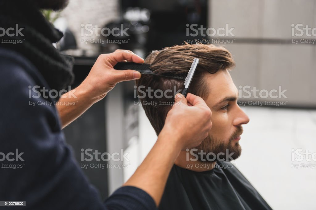 Male client getting haircut by hairdresser stock photo