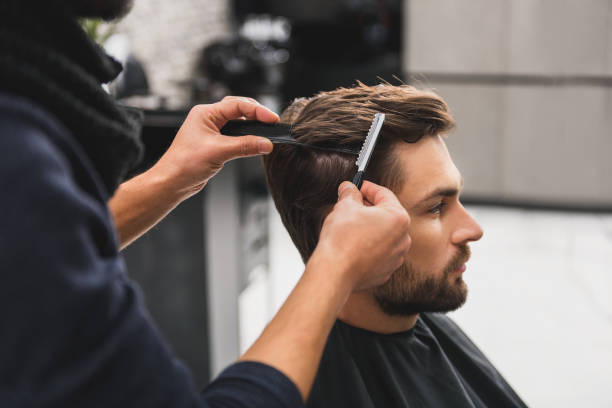 male client getting haircut by hairdresser - barbier coiffeur photos et images de collection