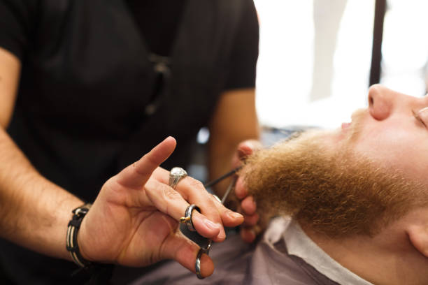 Male client having beard haircut at barbershop Professional hairdresser wearing black gloves cutting beard of client with scissors at barbershop. Bearded man getting beard haircut at barber salon shaving brush shaving cream razor old fashioned stock pictures, royalty-free photos & images