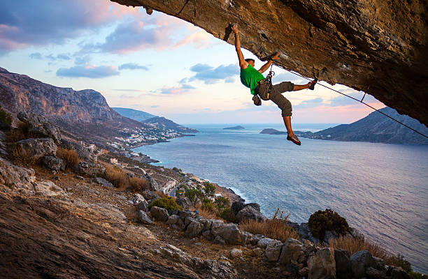 Male climber climbing overhanging cliff stock photo